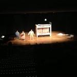 Foto de uma cena do espetáculo onde mostra um enorme beliche no centro do palco, com os três atores ao lado e vestindo pijamas e mais a esqueda, o pianista Tato Fischer.